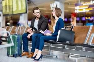 Reisende auf einer Bank am Flughafen lachen