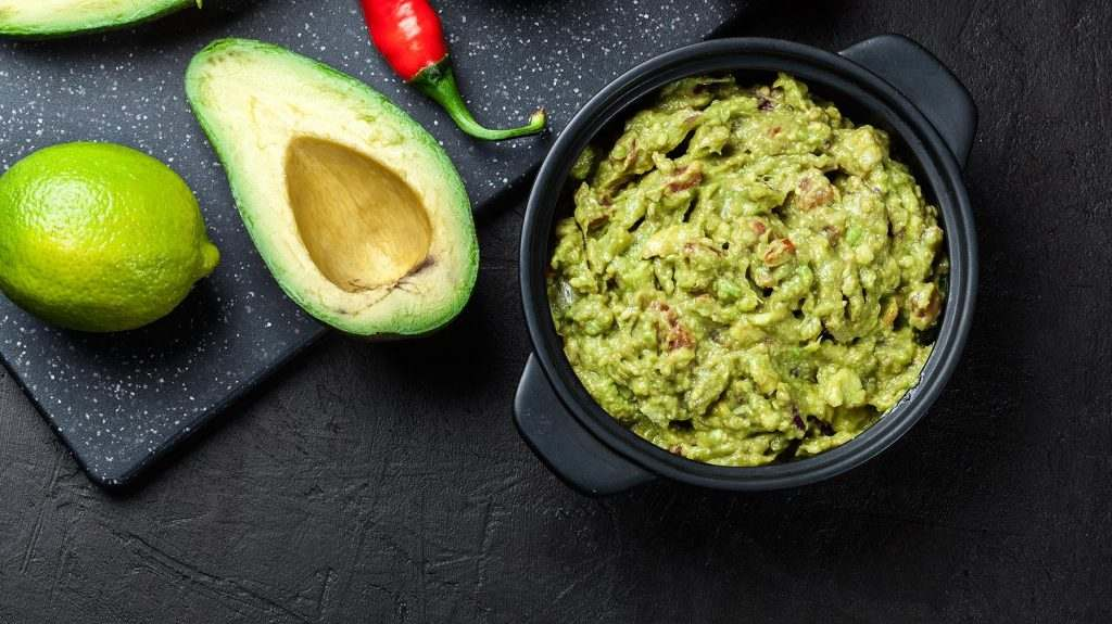 Bowl of guacamole with fresh ingredients on a black table