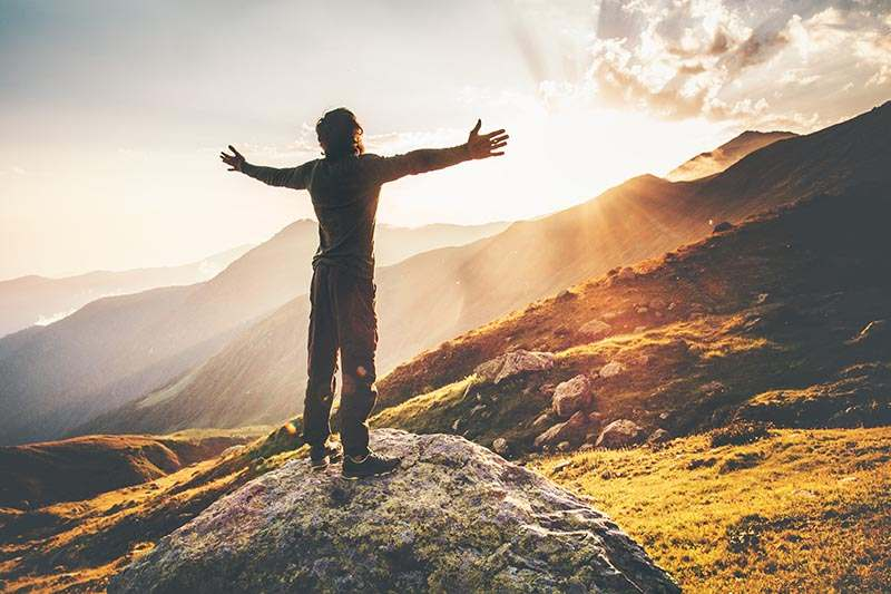 Happy Man raised hands at sunset mountains Travel Lifestyle emotional concept adventure summer vacations outdoor hiking mountaineering harmony with nature