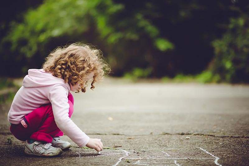 Child draws on asphalt