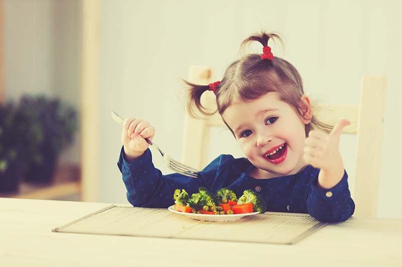 Kind beim Gemüse Essen, gücklich
