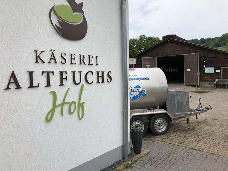 Käserei Altfuchshof Logo an Hauswand, im Hintergrund Bauernhof