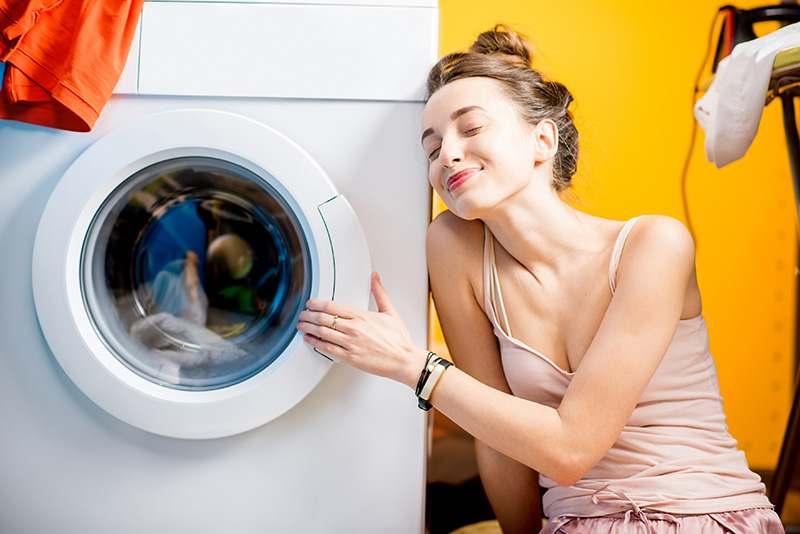 Frau lehnt zufrieden an ihrer Waschmaschine und wartet auf die Wäsche