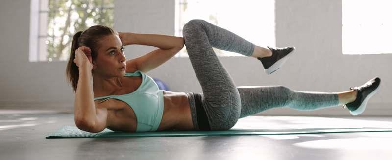 Junge Frau beim Sport, auf Matte, macht Crunches