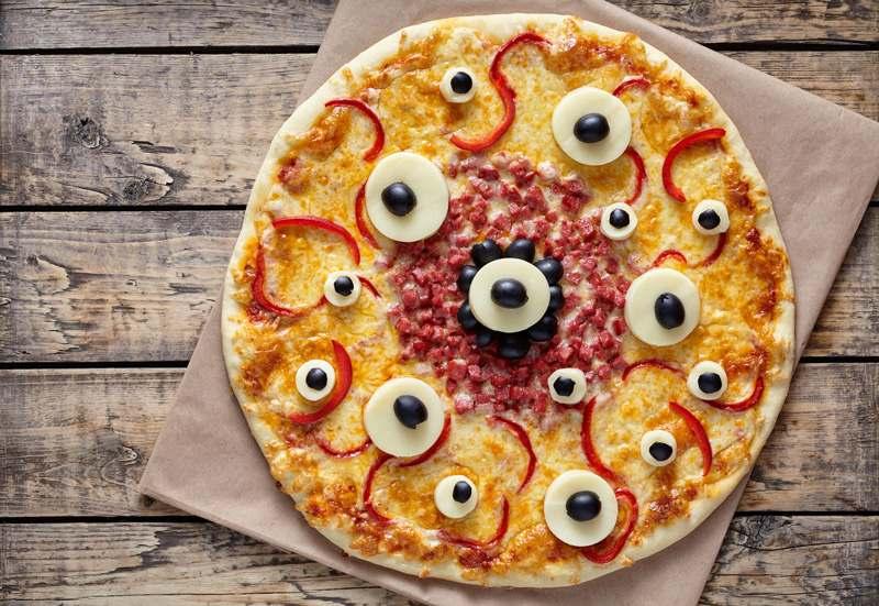 Pizza in Augen-Optik lecker belegt mit Ei, Oliven, Paprika und Schinkenwürfeln