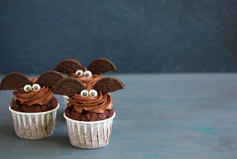 Cupcakes mit Schokotopping und Oreo-Keksen als Fledermausflügelchen