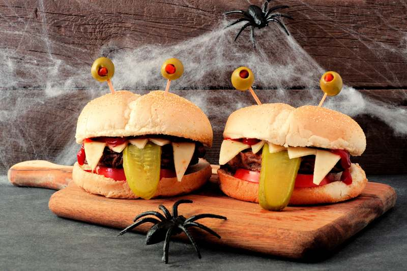 Burger, die dank Oliven als Augen und Käsezähnen wie Monster aussehen