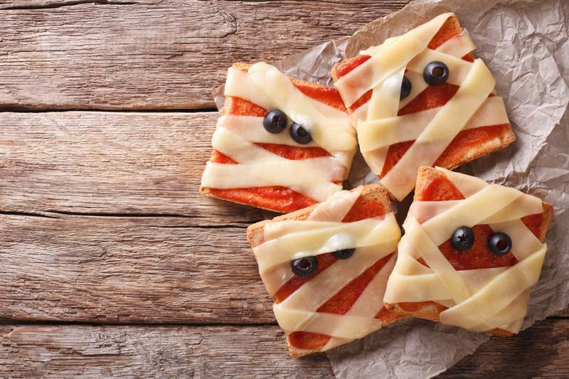 Toast mit Tomatemark, Käsestreifen und Oliven als Augen