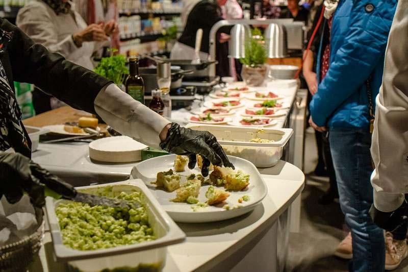 Anrichten von Feta Käse mariniert auf Brot, im Hintergrund Rinderschinken mit Balsamico Creme
