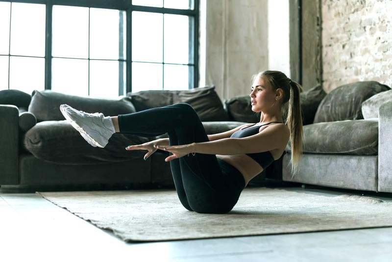 Junge Frau beim Trainieren auf dem Teppich vor der Couch zu Hause