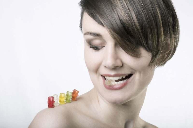 Frau mit Gummibärchen auf der Schulter und einem im Mund