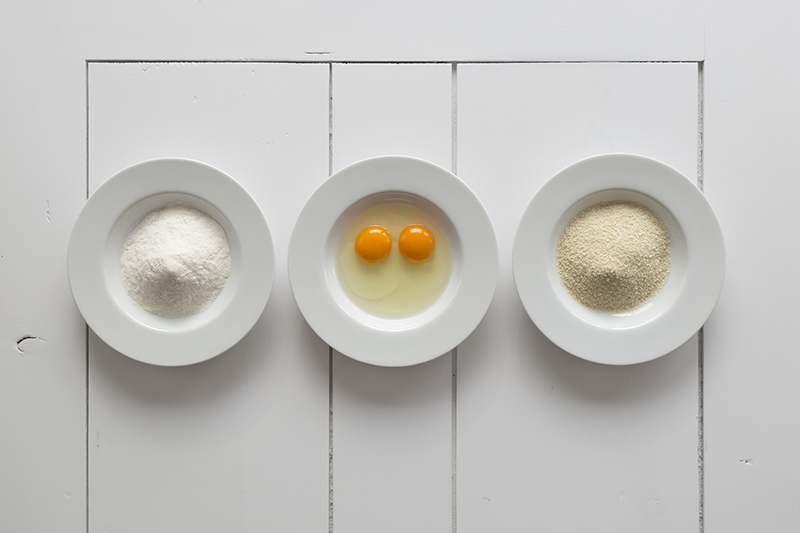 Teller mit Mehl, Teller mit Ei und Teller mit Paniermehl oder Semmelbrösel