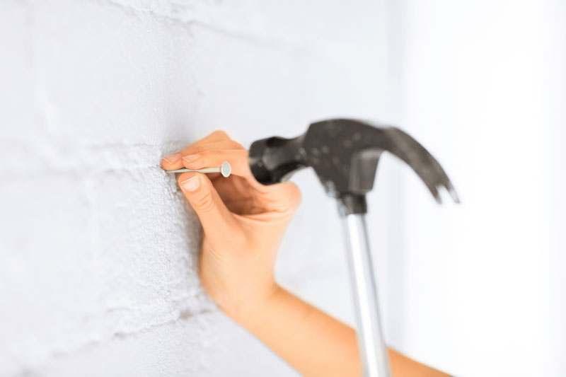 Ansatz zum Nagel in die Wand hauen