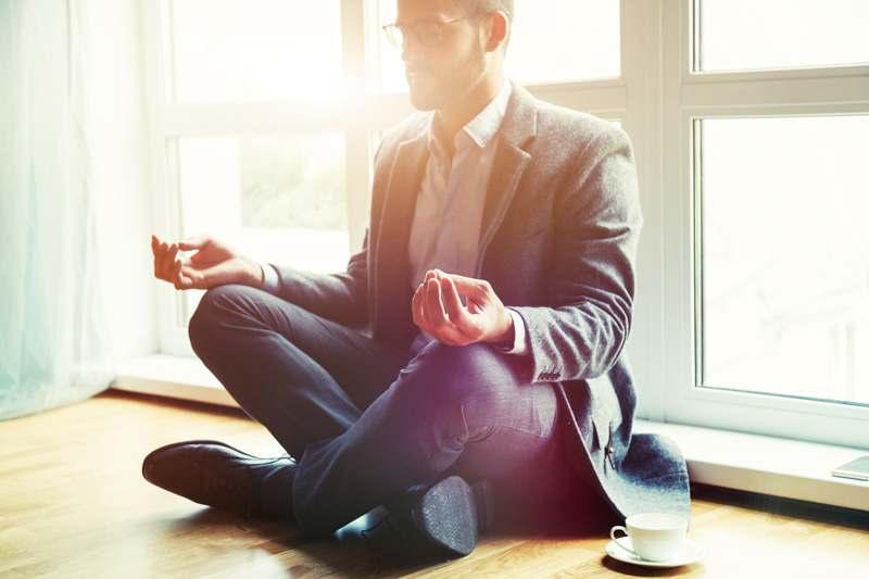 Büromann beim Yoga im Anzug mit einer Tasse Kaffee